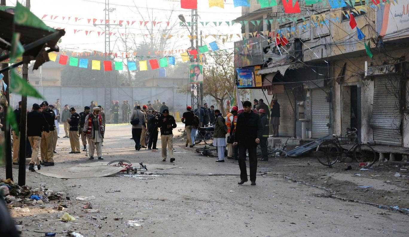 Pakistani security officials inspect the site of a suicide bomb attack in Rawalpindi, on Monday.