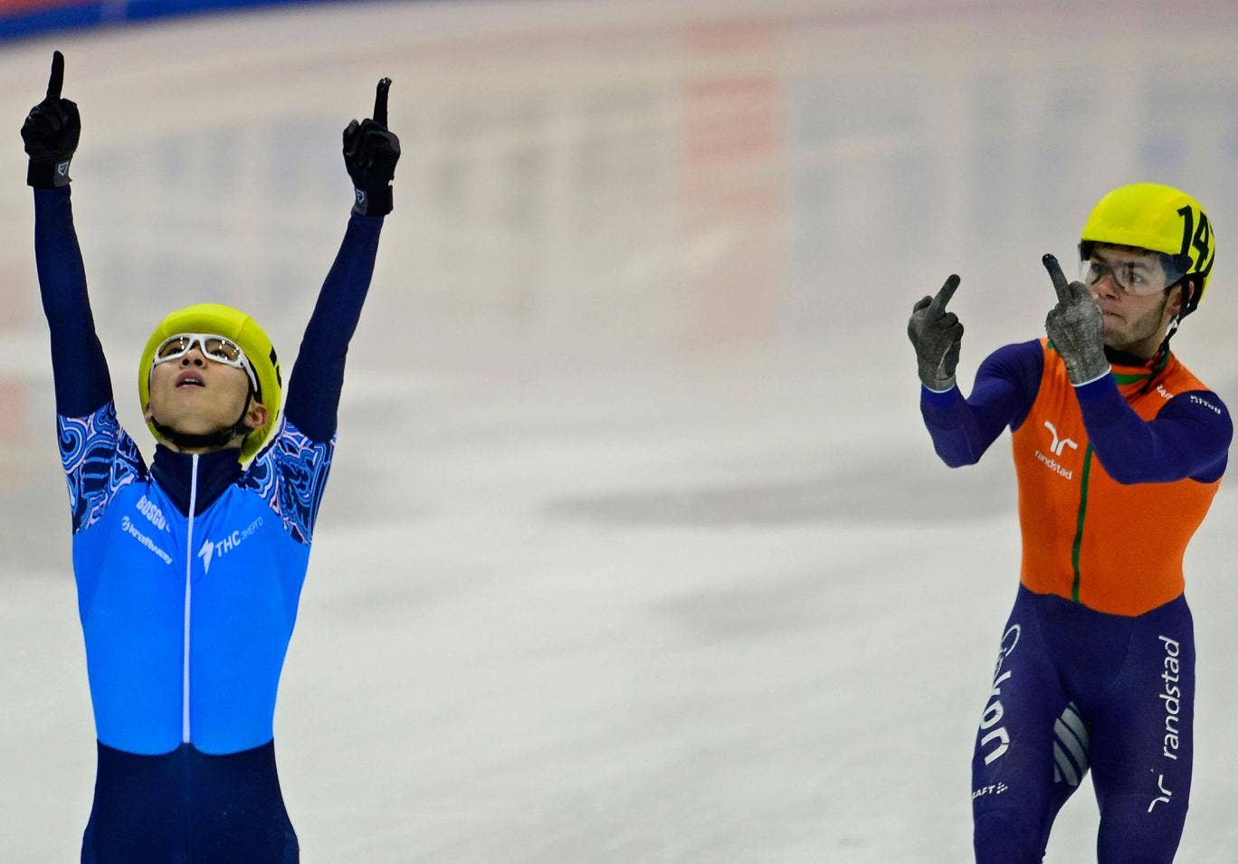 Sjinkie Knegt (R) of the Netherlands' team gestures next to Victor An (L) of the team of Russia celebrating after Russia won the men's 5000m relay final race of the ISU European Short Track speed skating Championships in Dresden, eastern Germany, on Janua