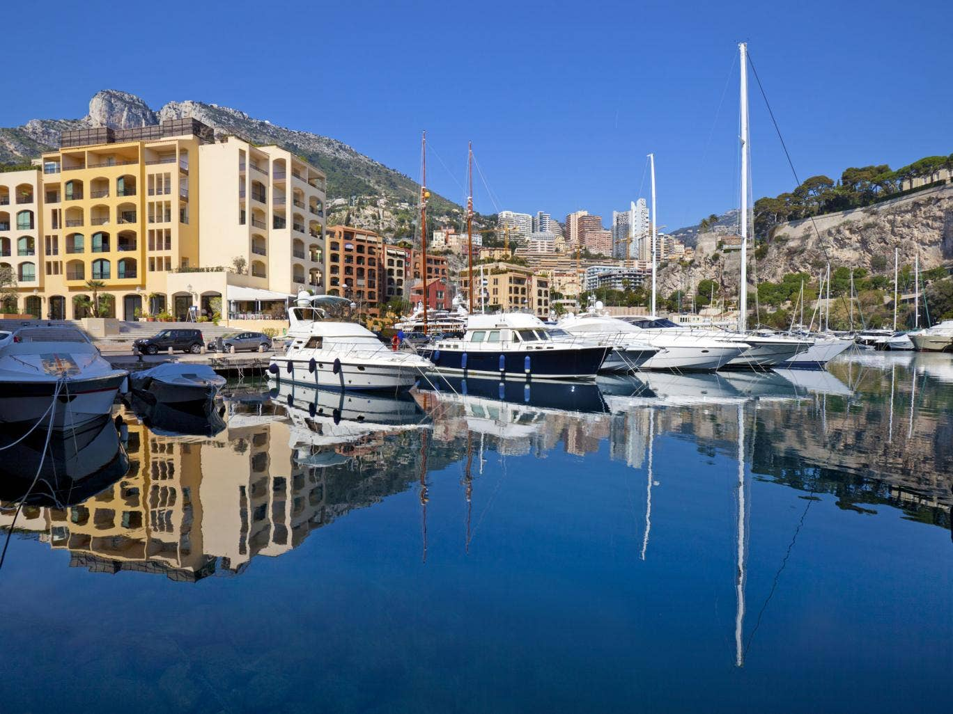 Luxury yachts and apartment buildings reflected in the calm waters of Fontvieille harbor, Monaco