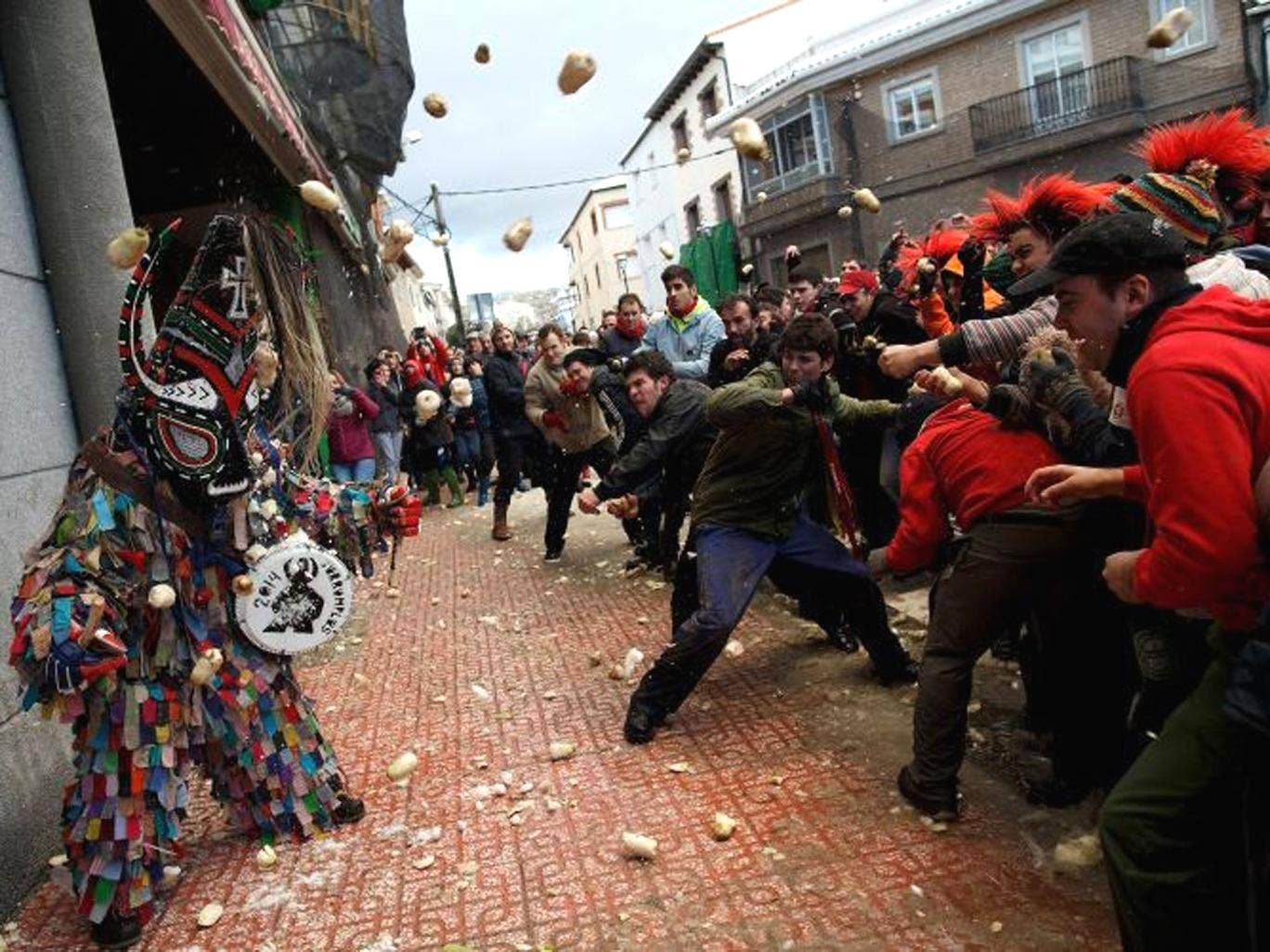 People throw turnips at the Jarramplas as he makes his way through the streets beating his drum during the Jarramplas Festival in Piornal