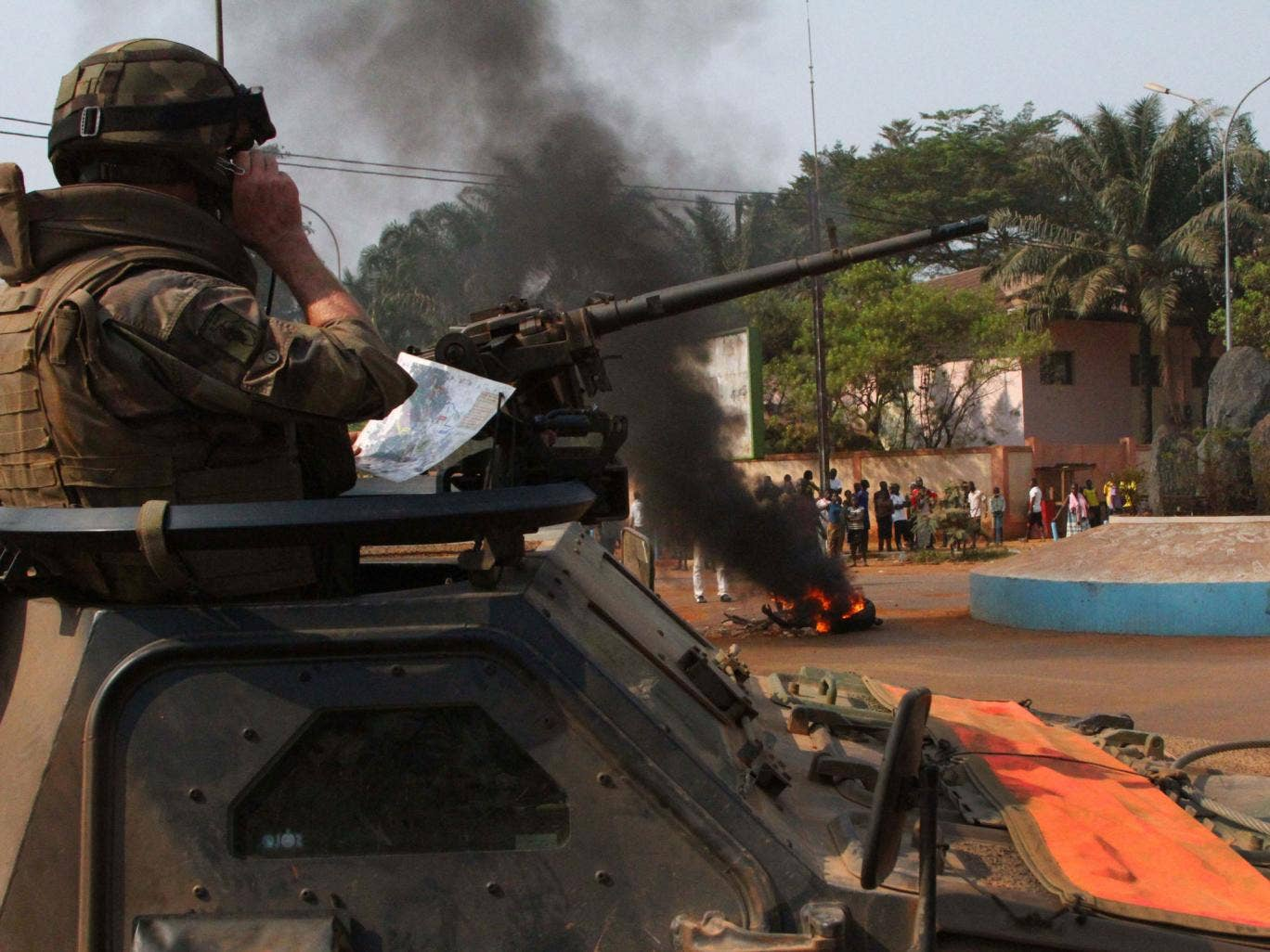 A French soldier looks on as the body of a lynched Muslim man is burned by a crowd, in Bangui; the EU has decided to send out troops to help stabilise the country