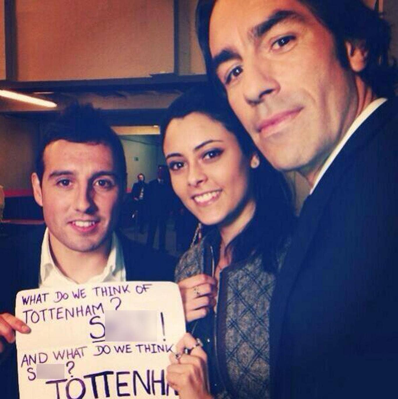 Current Arsenal midfielder Santi Cazorla and former player Robert Pires pose with a female fan holding an expletive-ridden chant aimed towards Tottenham supporters