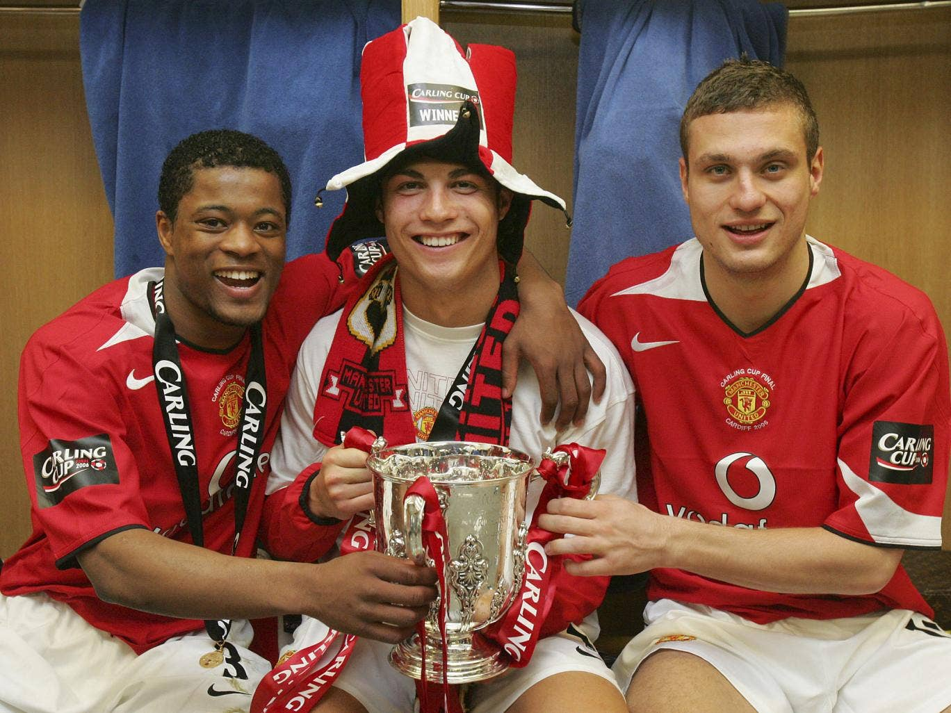 Patrice Evra, Cristiano Ronaldo and Nemanja Vidic of Manchester United pose with the Carling Cup trophy in the dressing room after their 2006 win