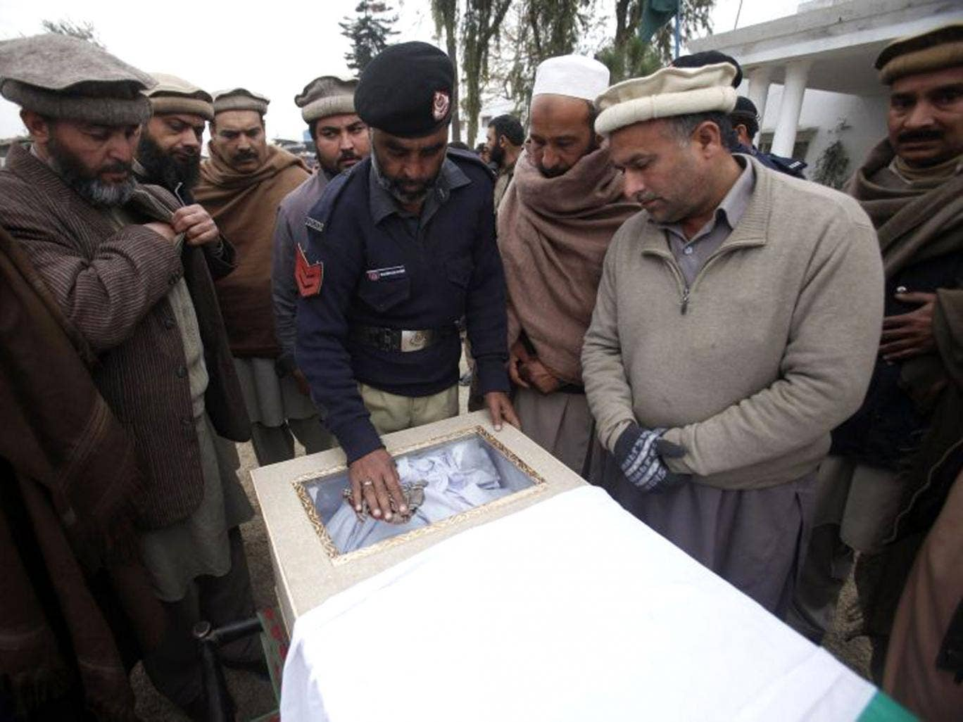 A policeman and relatives gather around the flag-draped casket of a policeman, who was killed in a bomb attack, during a funeral ceremony at the Police Line, or the police's main office, in Charsadda, on the outskirts of Peshawar