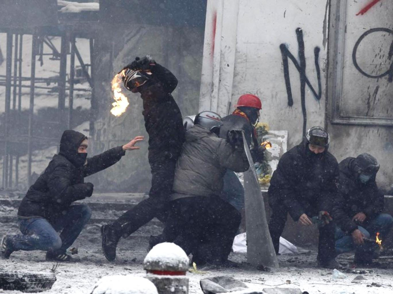 A pro-European protester throws a Molotov cocktail towards riot police during clashes in Kiev