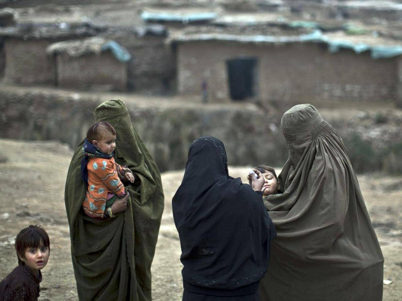 A Pakistani health worker gives a polio vaccine to children in a poor neighborhood that hosts displaced people from Pakistani tribal areas and Afghan refugees, on the outskirts of Islamabad, Pakistan