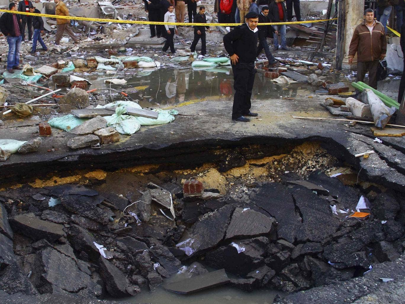 A police officer inspects a crater made after a bomb attack in front of Cairo Security Directorate building
