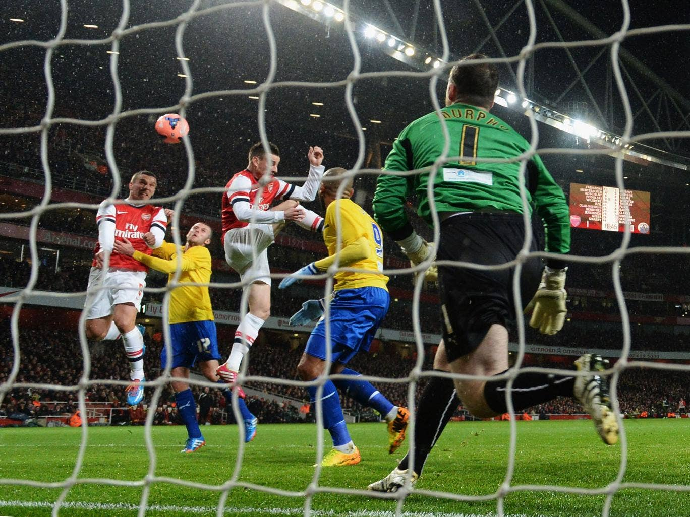 Lukas Podolski of Arsenal rises to score the second goal of the evening with a header