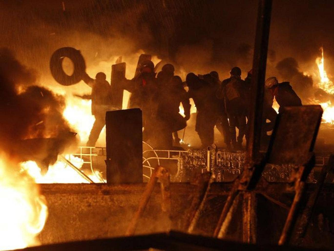 Anti-government protesters throw tyres at the site of clashes with riot police in Kiev