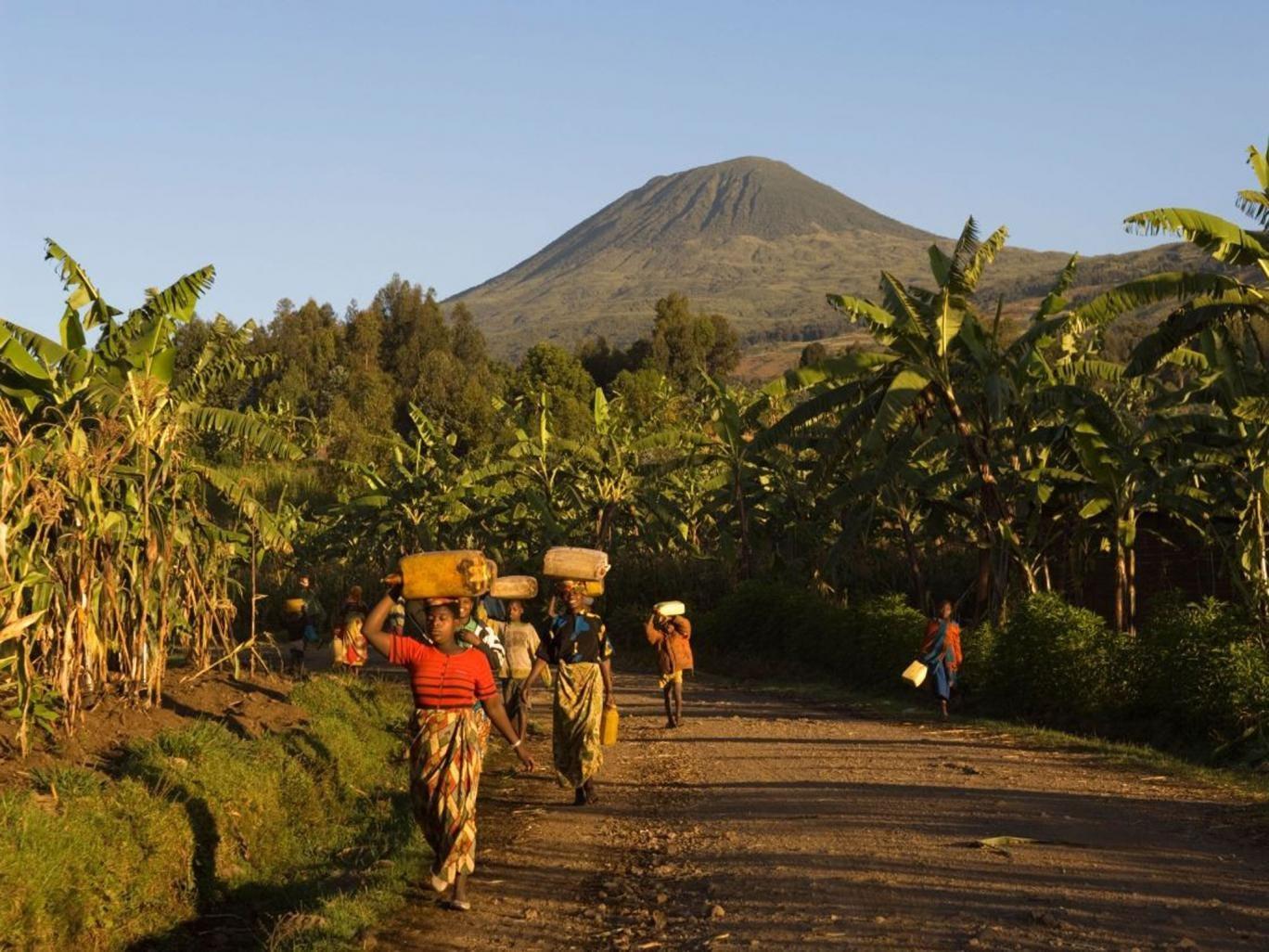 Women walk home with dormant volcano Muhabura in the background