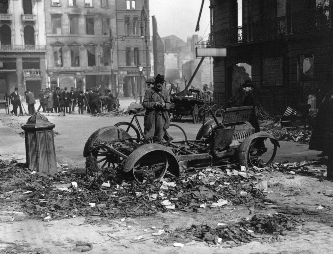 The aftermath of the Easter uprising with the ruins of a car in the foreground which has been used as a barricade