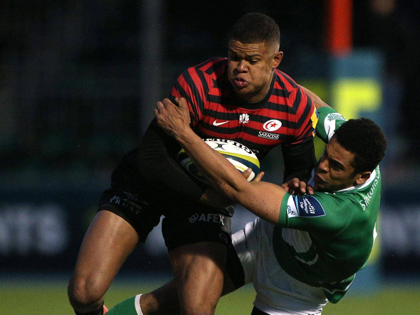 Saracens' Nathan Earle is held by Zach Kibirige during the game on Sunday