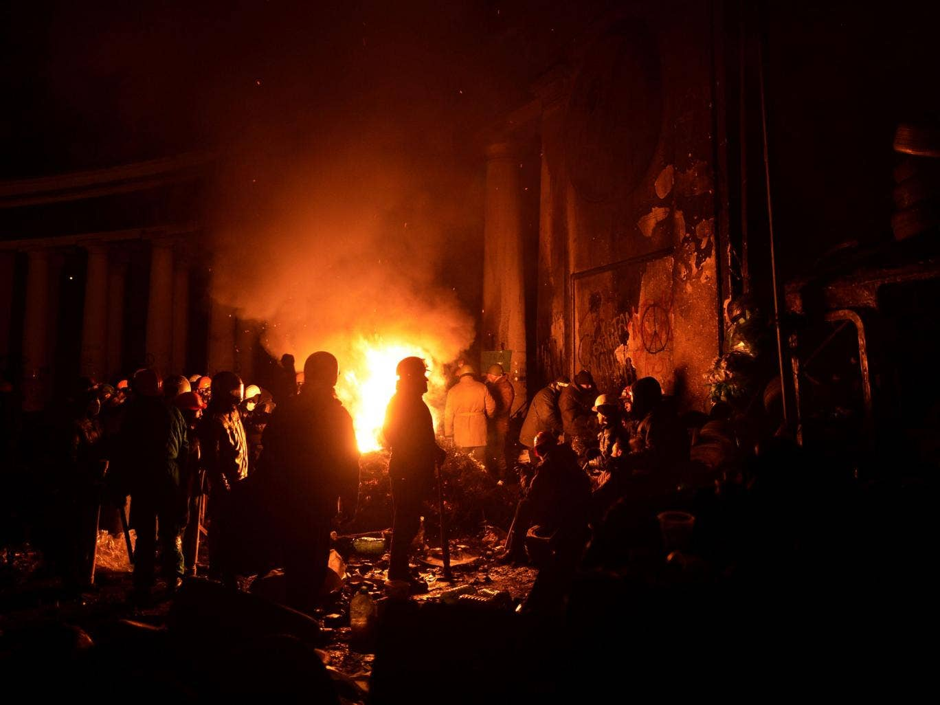 Anti-government protesters gather around a fire to get warm at a road block in Kiev on Sunday night
