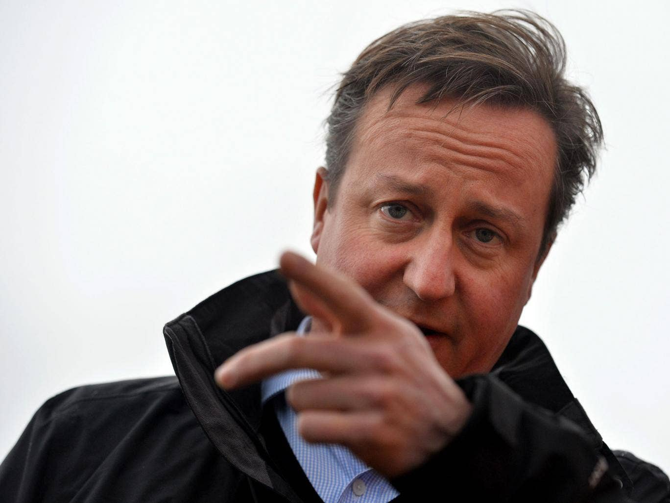 Britain's Prime Minister David Cameron gestures as he speaks to local firefighters in the village of Yalding during a visit on December 27, 2013 in Yalding, England. Mr Cameron spoke to residents in the village in southeast England that was effected by fl