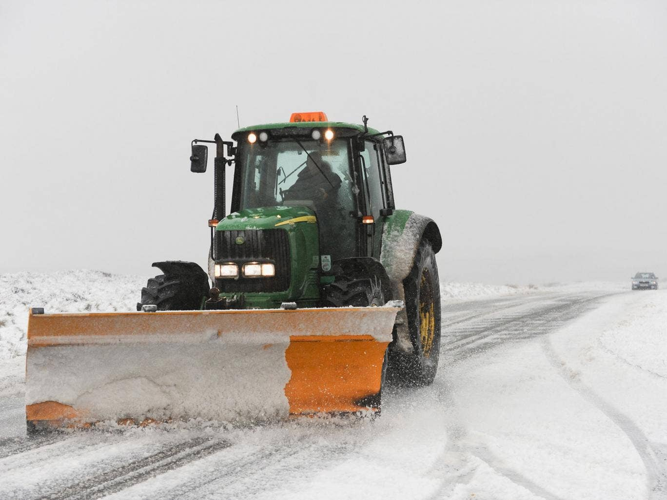A tractor snow plough tries to keep the road open as heavy snow falls on the North Yorkshire Moors near Castleton