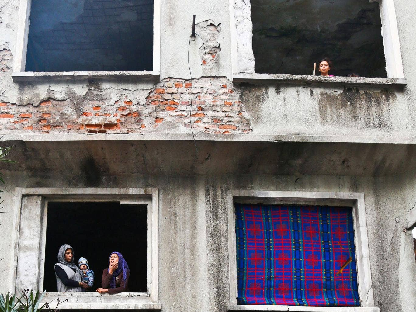 Syrian refugees look out from an evacuated house in Istanbul. Hundreds of Syrian refugees will be allowed to come to Britain under new government plans