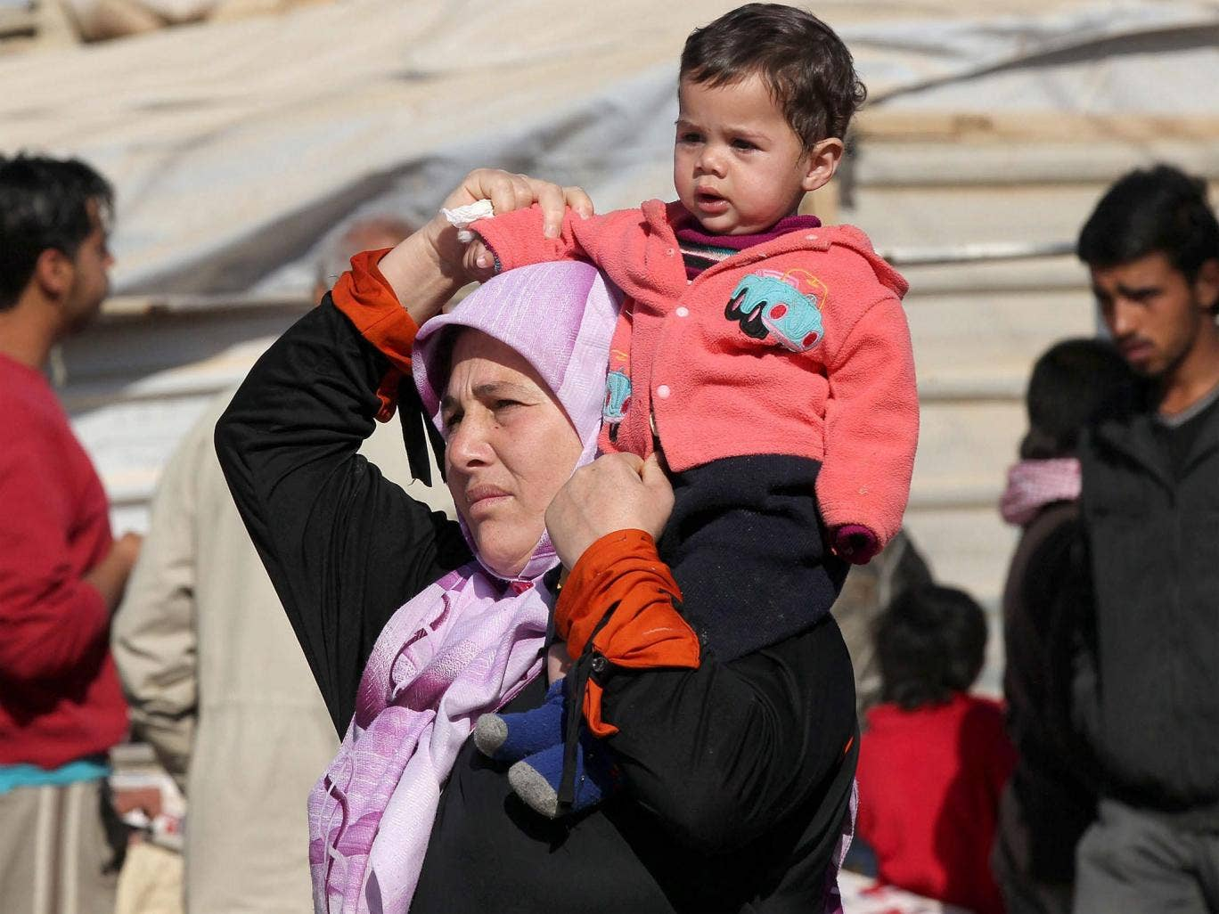 A Syrian woman carries a child on her shoulder at a refugee camp in Jordan