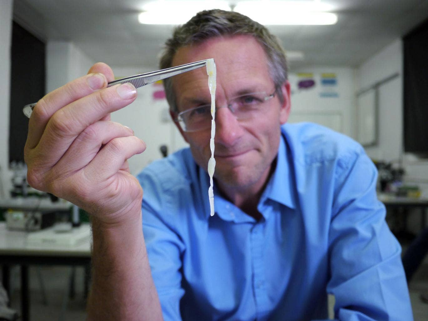 Michael Mosley holding up a piece of human tapeworm as Mosley lived with tapeworms in his guts for six weeks for a documentary