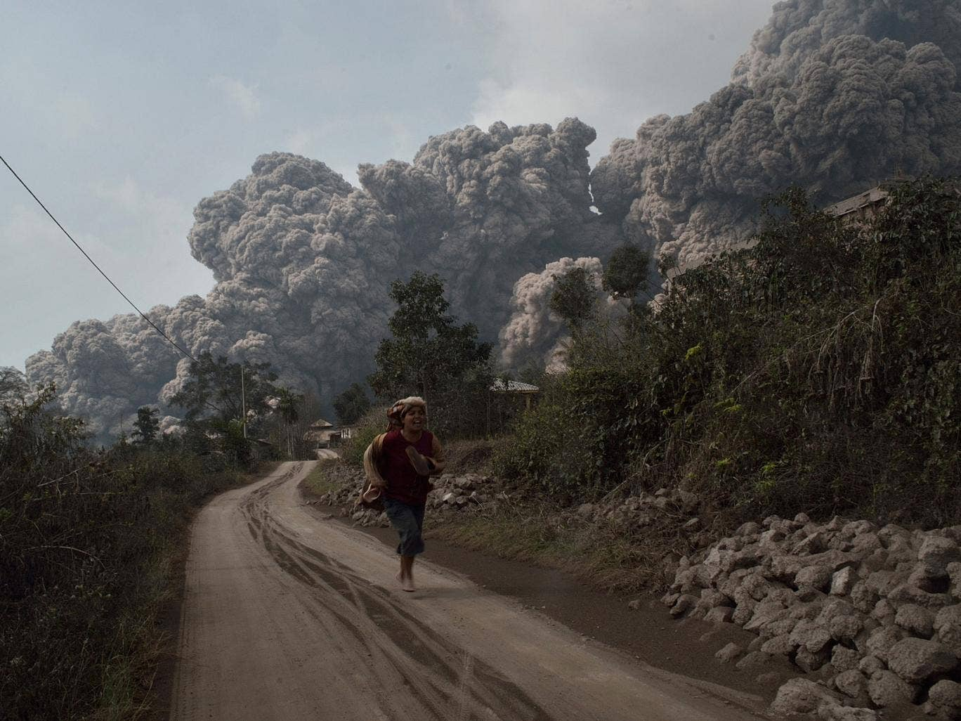 A resident runs away to escape from hot volcanic ash clouds engulfing villages in Karo district during the eruption of Mount Sinabung volcano in Sumatra.