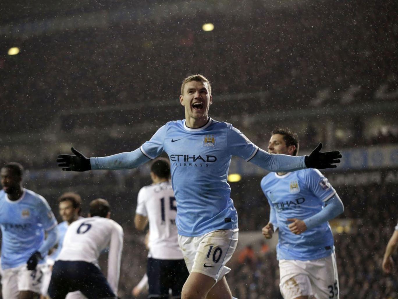 City slicker: Edin Dzeko celebrates scoring City's third goal against Tottenham