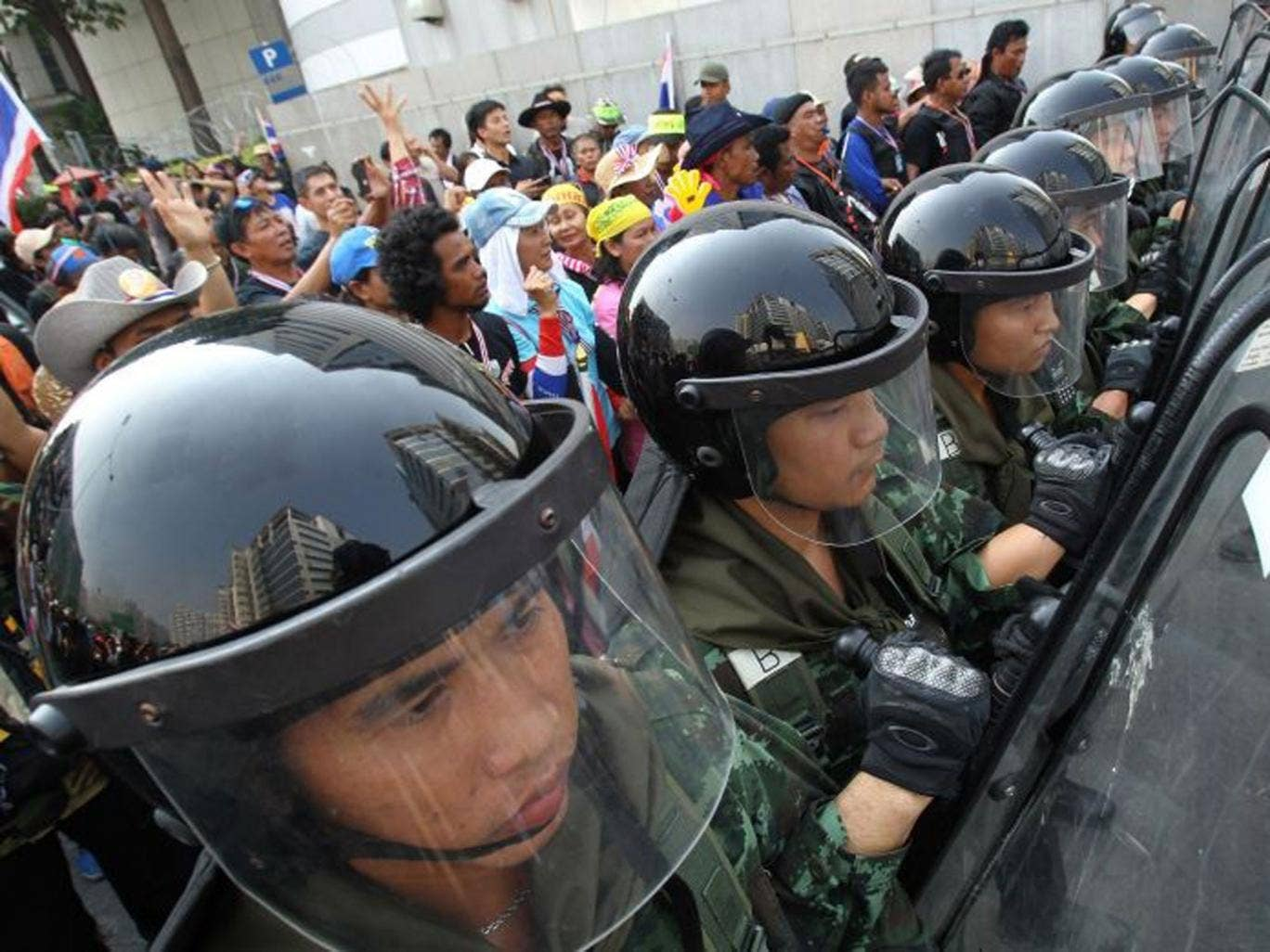 Thai soldiers stand guard to block anti-government protesters (left) during a rally outside the office of the permanent secretary for defense where Prime Minister Yingluck Shinawatra was reportedly working inside