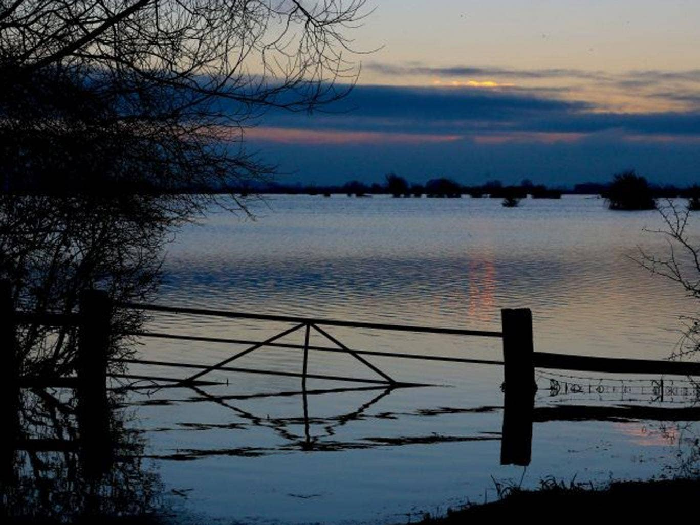 The sun rises over flood water still present in fields on the Somerset Levels near Langport