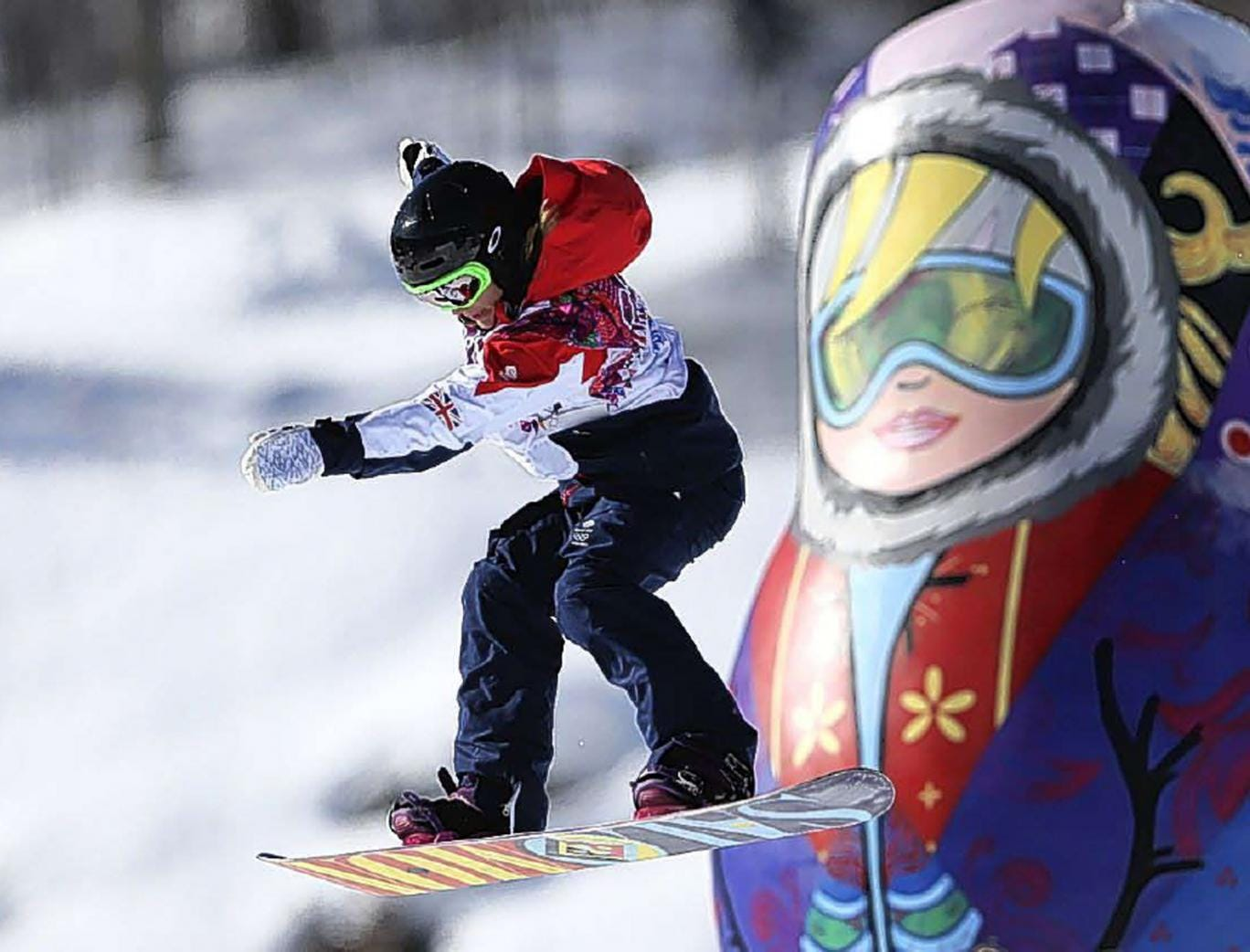 A competitor takes a jump past a giant matryoshka doll during a snowboard slopestyle training session at the Rosa Khutor Extreme Park in Krasnaya