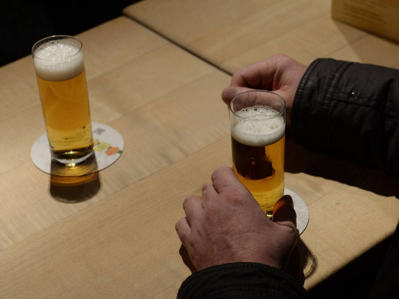 A client holds a glass of Cologne 'Koelsch' beer on November 7, 2013 in Cologne, western Germany.