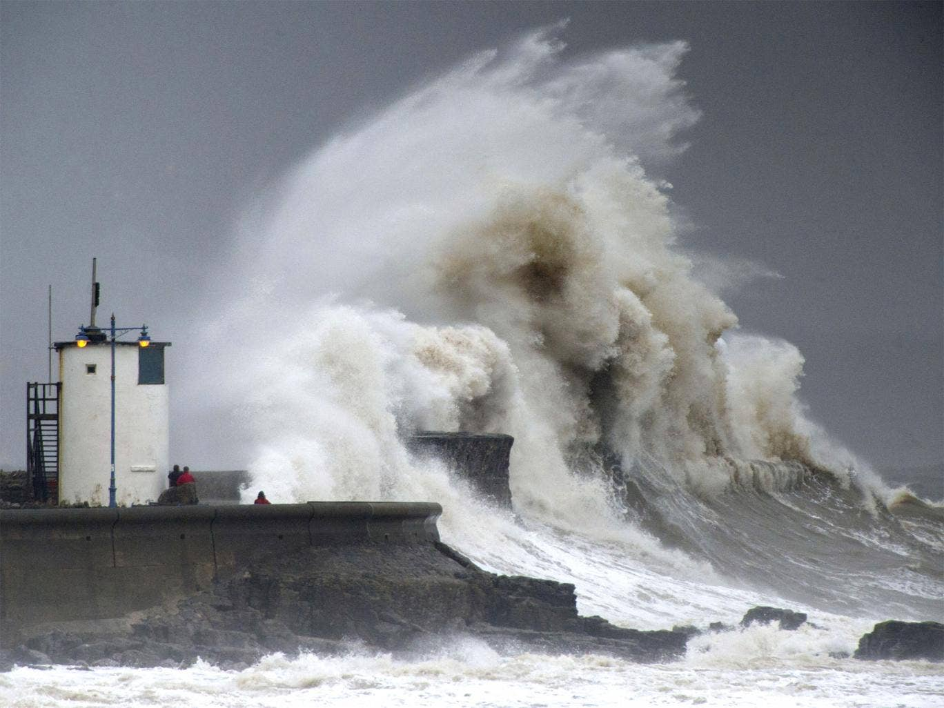 Spectators watch as waves break over the harbour wall at Porthcawl, Wales, during a high tide