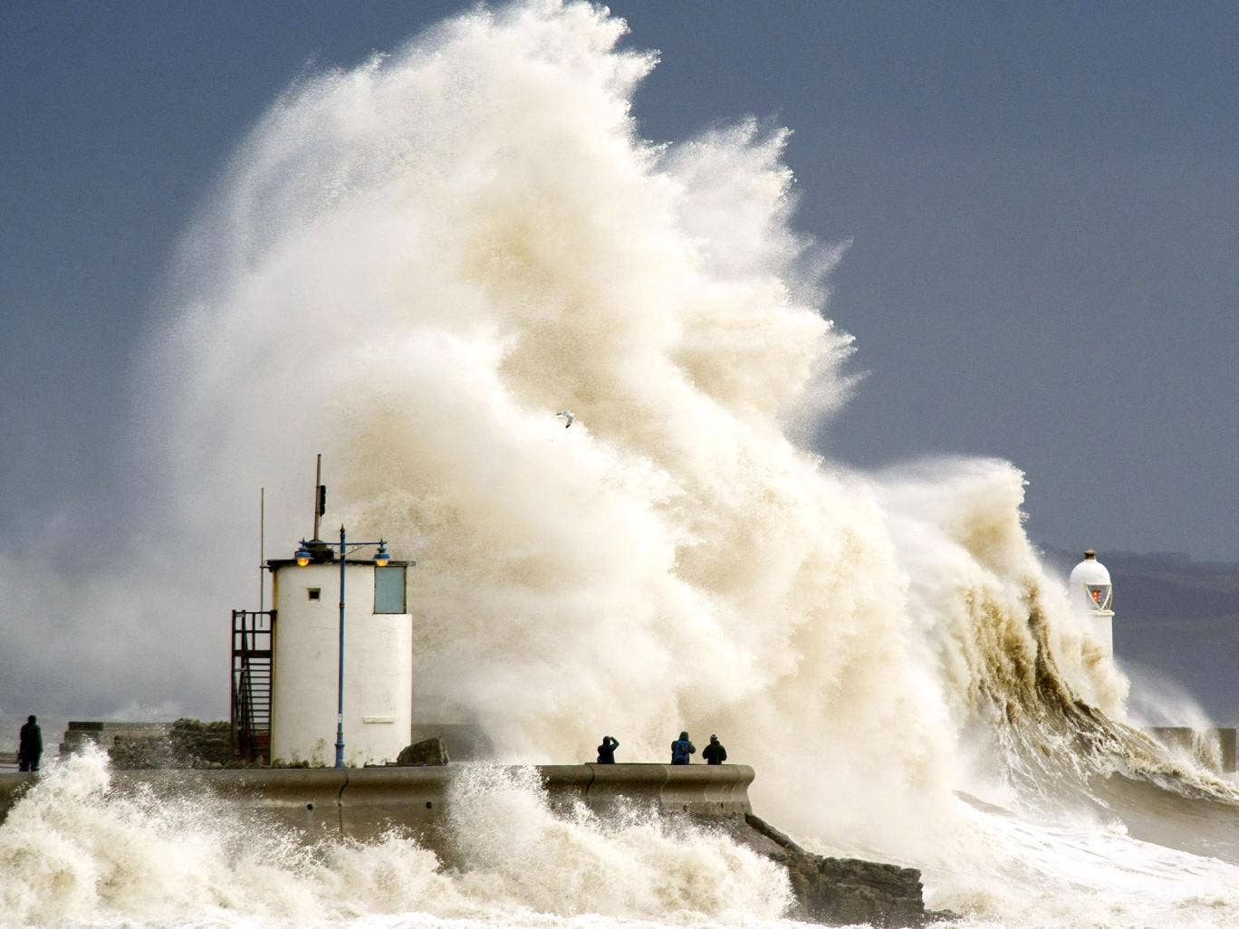 Spectators watch as waves break over the harbour wall at Porthcawl during a high tide in Porthcawl