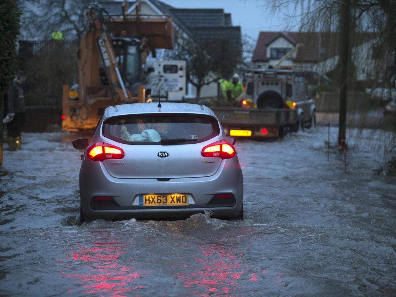 A car drives through rising flood waters as it leaves the village of Moorland on the Somerset Levels near Bridgwater
