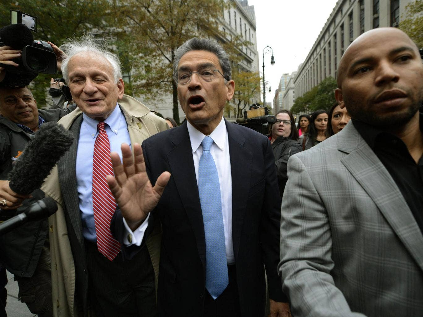 Rajat Gupta, centre, leaves court in New York after being sentenced for passing on secrets