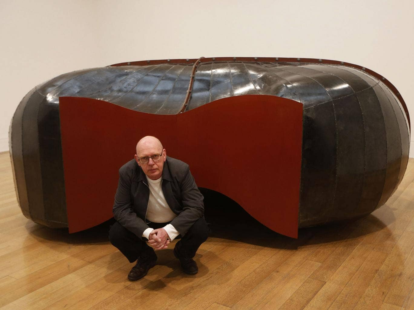 British artist and Turner Prize winner Richard Deacon poses with his sculpture 'Struck Dumb 1988' at Tate Britain