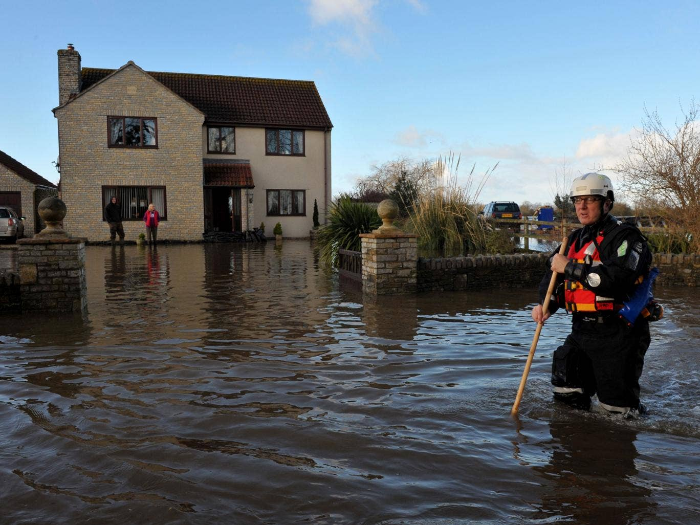 An emergency worker walks down the road outside a property in Moorland, Somerset, after residents were advised to evacuate after flood defences were breached overnight