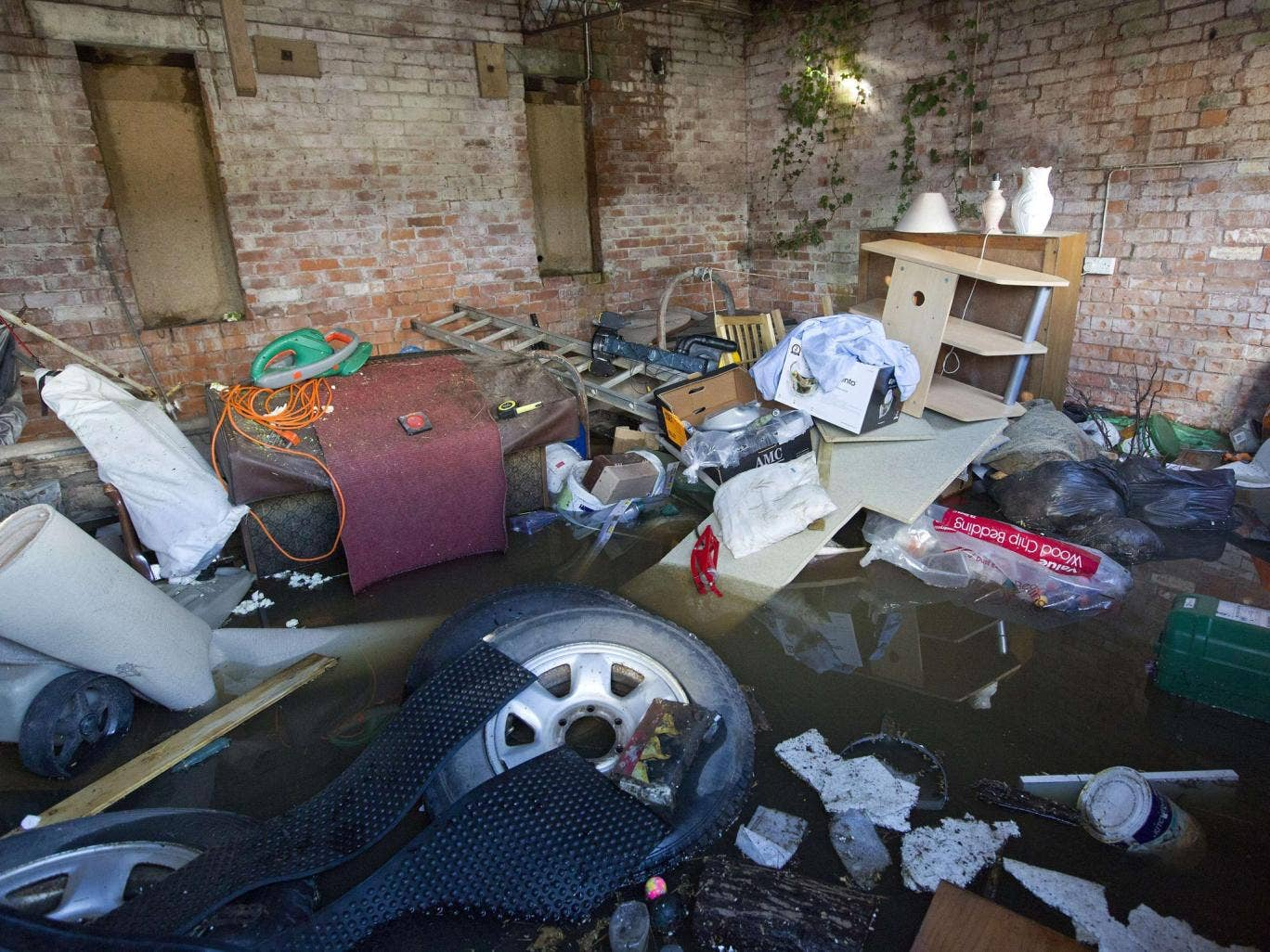 Belongings are seen, piled up in a outhouse which has been surrounded by flood water in Moorland