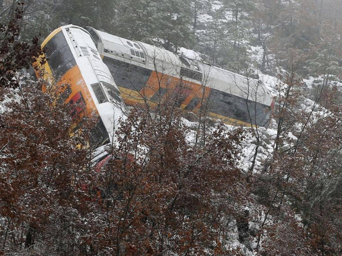 The train hangs from a ledge after it had been derailed by a boulder