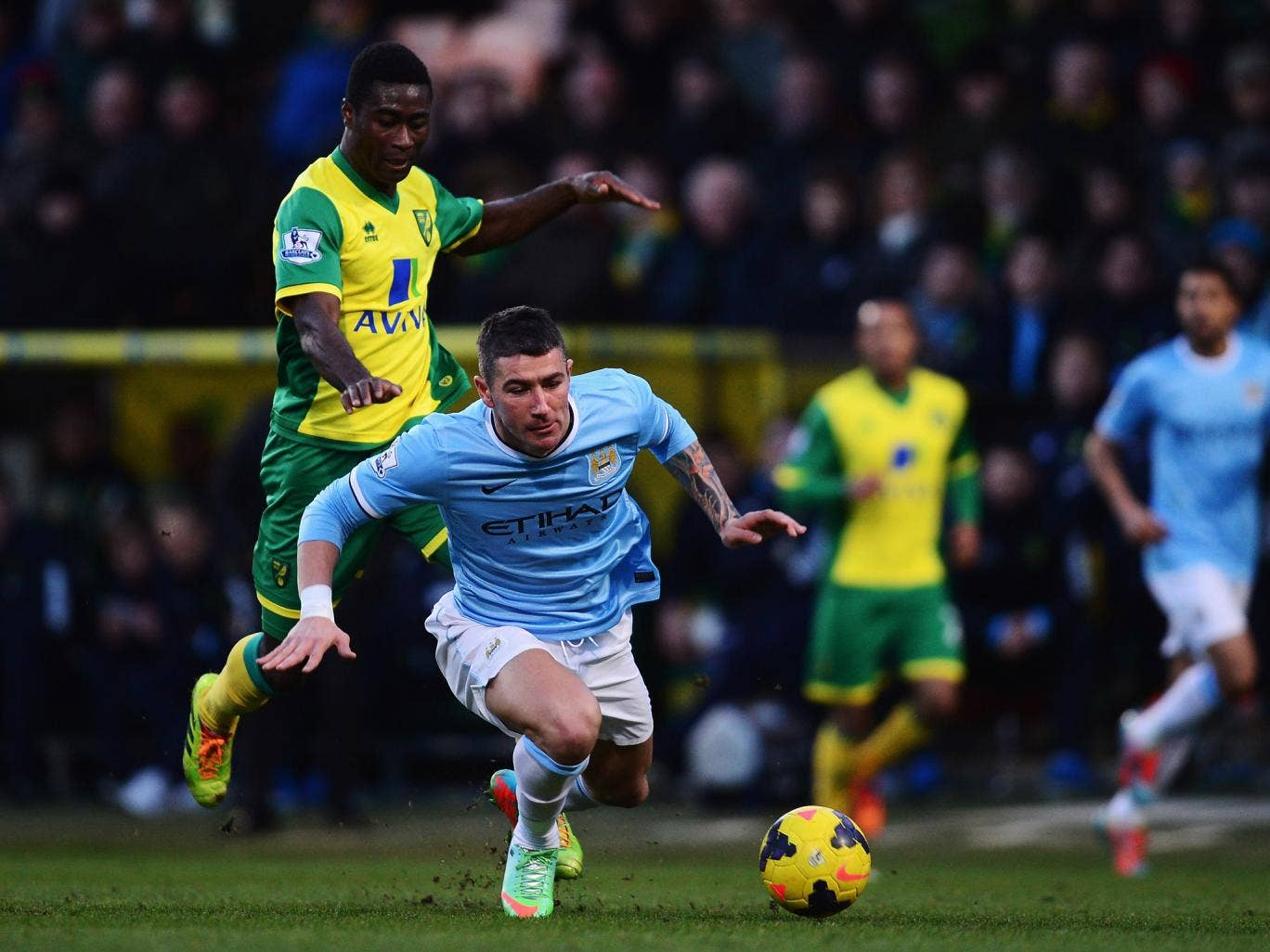 Manchester City defender Aleksandar Kolarov falls to the under pressure from Norwich midfielder Alexander Tettey