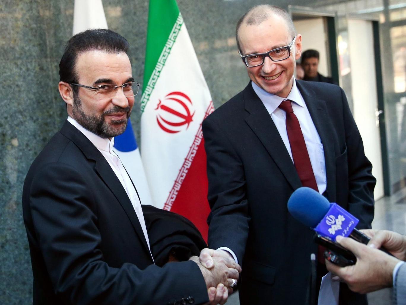 The deputy head of the International Atomic Energy Agency (IAEA), Tero Varjoranta (R), and Iranís IAEA envoy Reza Najafi (L) shake hands after an agreement reached, in Tehran, Iran
