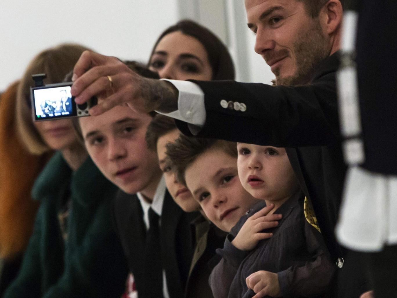 David Beckham photographs his children on the front row