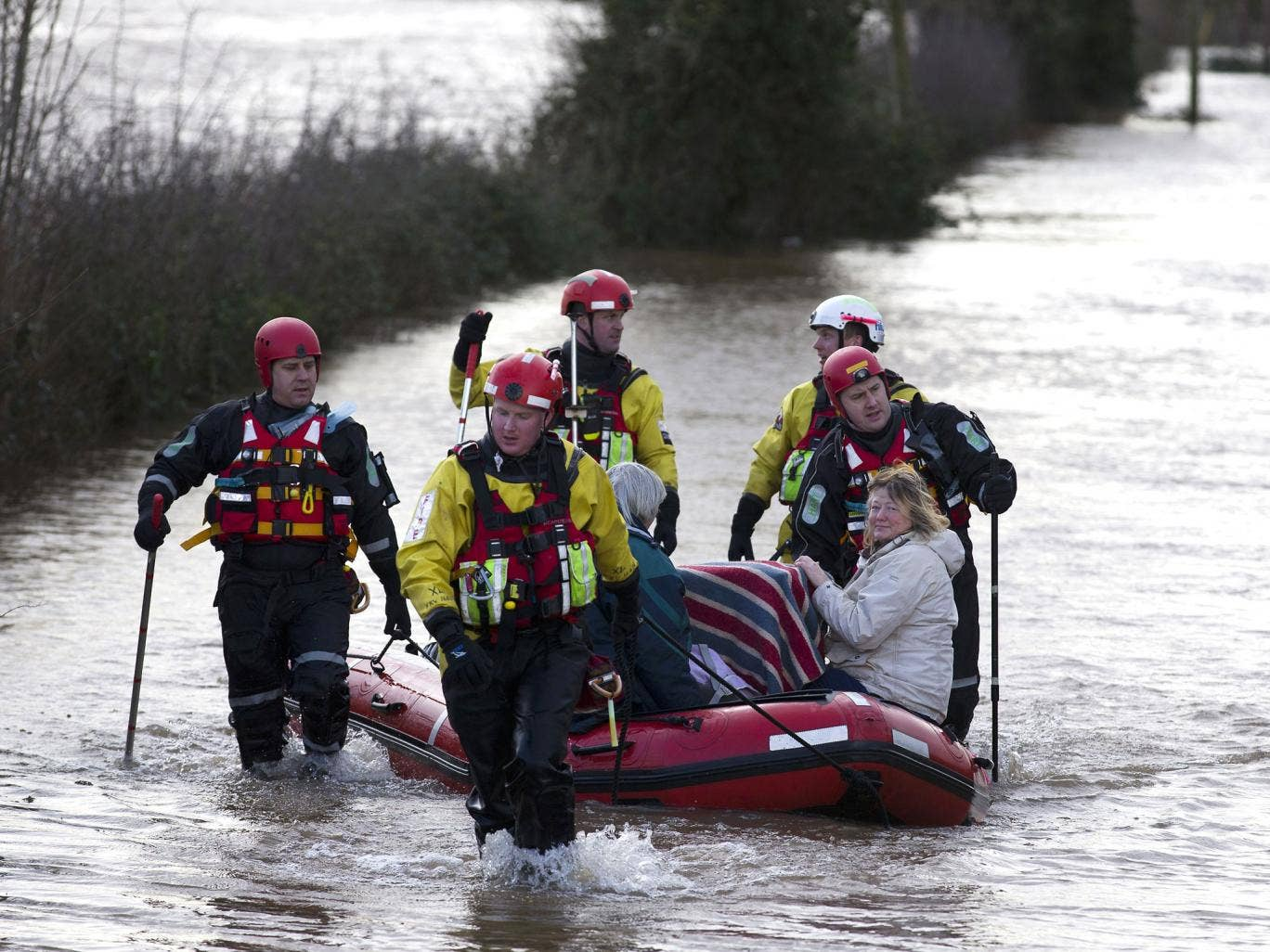 Devon and Somerset Fire and rescue service evacuate two women and two cats in baskets through flood waters in Burrowbridge