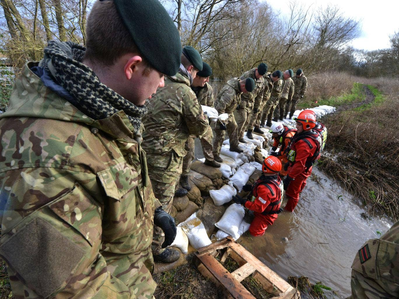 Reserve soldiers of 7 Battalion The Rifles, deployed alongside members of Berkshire Fire and Rescue Service, working hard to dam a breach in the Kennet Canal that threatened an electrical sub-station near Burghfield, south of Reading, as the military were