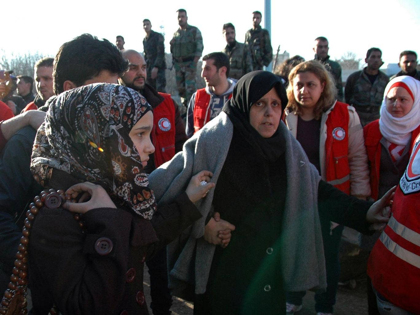 Two women walk towards a bus to evacuate the battleground city of Homs, Syria