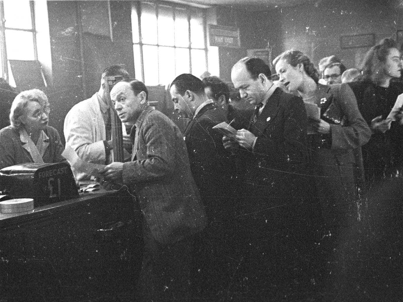 Guessing game: punters line up to place bets the old-fashioned way at London's White City Greyhound Racing Stadium in 1943