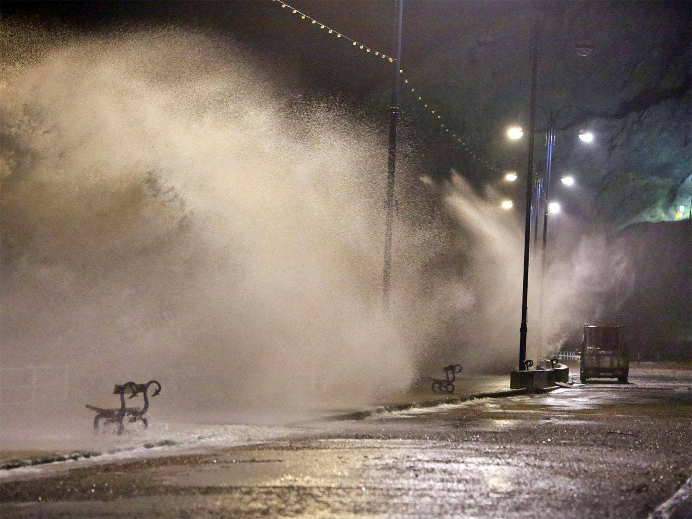 Waves break over the sea wall in Aberystwyth, west Wales