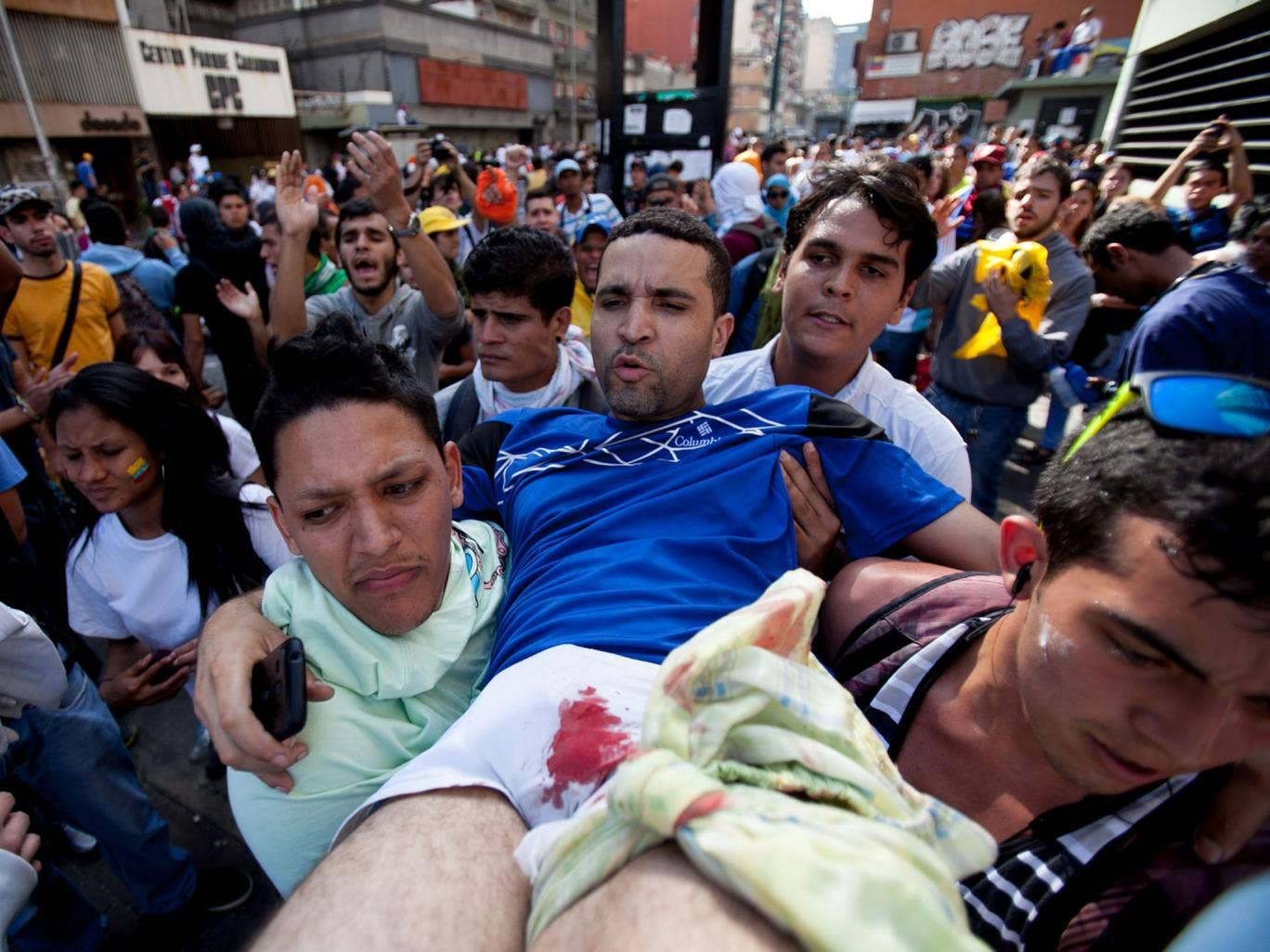 A demonstrator with a gun shot wound to his left leg is carried to safety after clashes broke out in Caracas