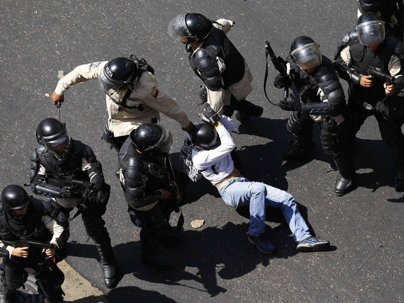 A demonstrator is detained after jumping over a riot police line during an anti-government protest in Caracas