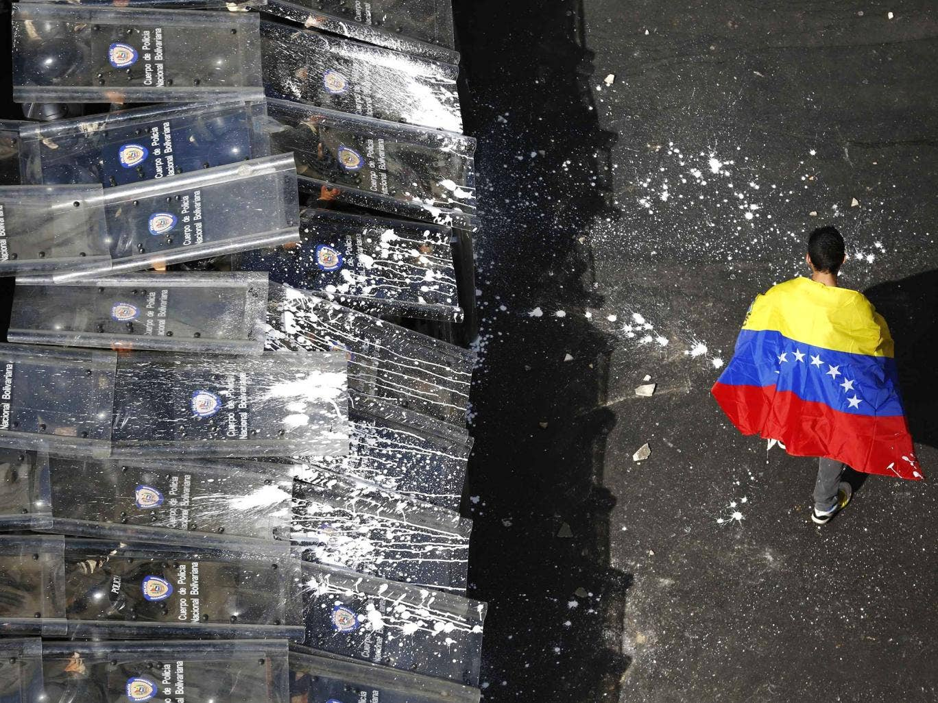 A demonstrator with a Venezuelan flag draped around himself protests against the government of Venezuela's President Nicolas Maduro, in front of a riot police line in Caracas