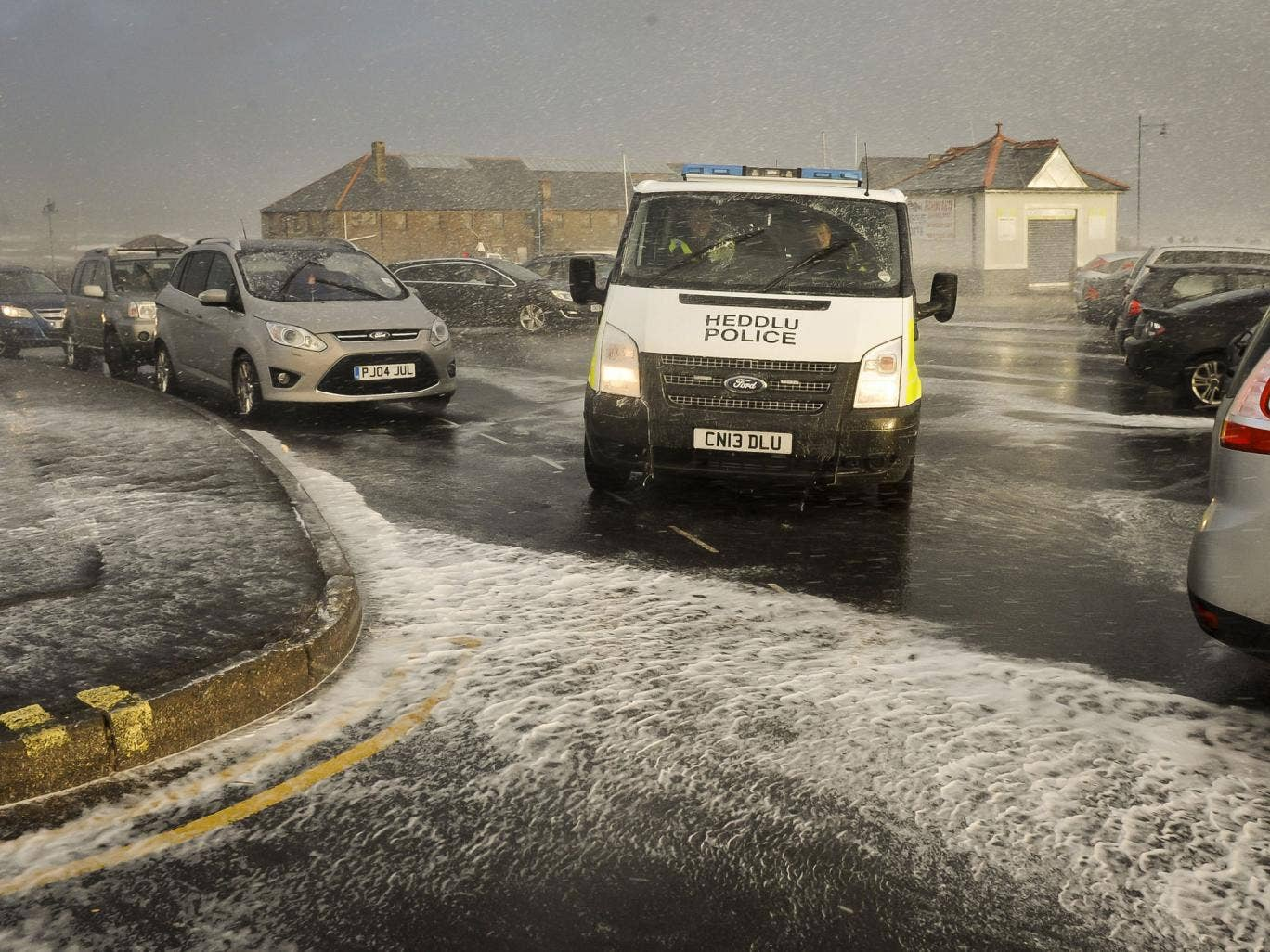 A police van makes its way through the sea spray and foam on the Esplanade, Porthcawl, south Wales (Wednesday), as the region continues to be battered by high winds and heavy rain