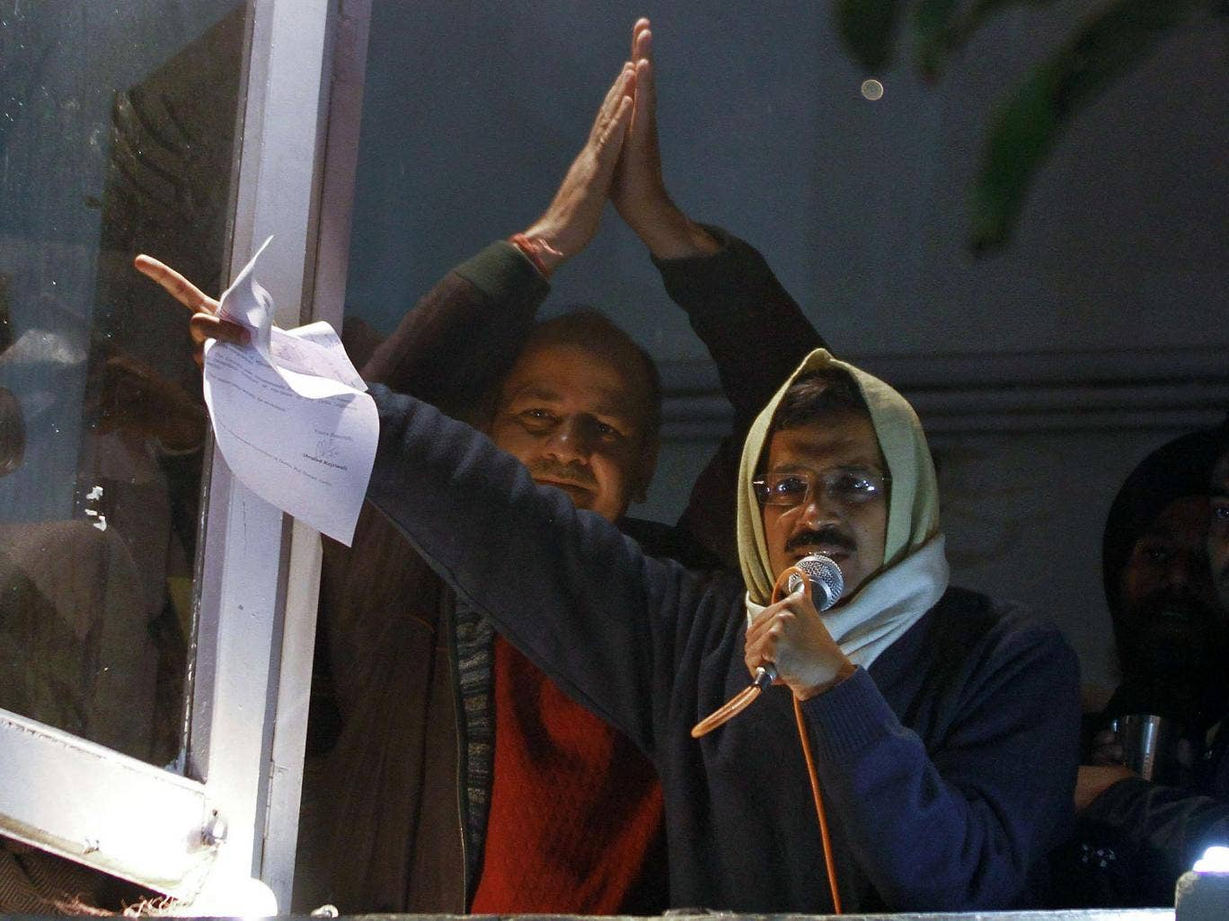 Delhi's Chief Minister Arvind Kejriwal waves his resignation letter as he addresses supporters at Aam Aadmi (Common Man) Party offices
