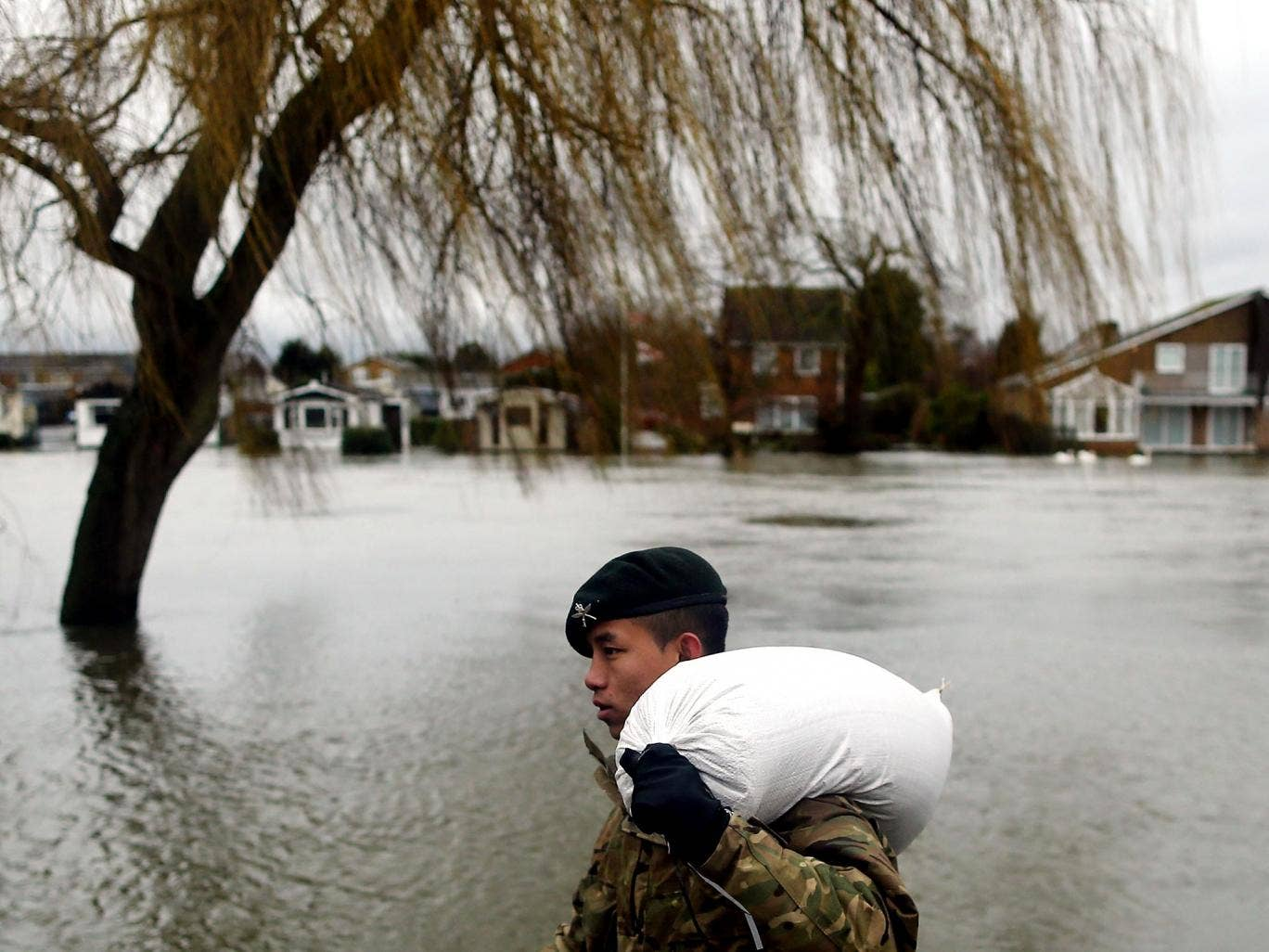 A Gurkha helps to place sandbags outside homes along the Thames in Staines yesterday